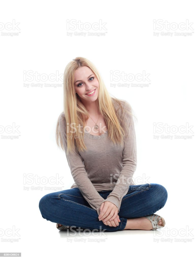 224b3570 Full length portrait of a blonde girl wearing casual clothes, seated pose.  isolated against white background. - Stock image .