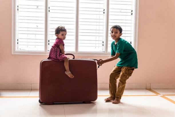 in voller länge portrait eines jungen ziehen einen koffer mit einem babyjungen - kleinkind busy bags stock-fotos und bilder