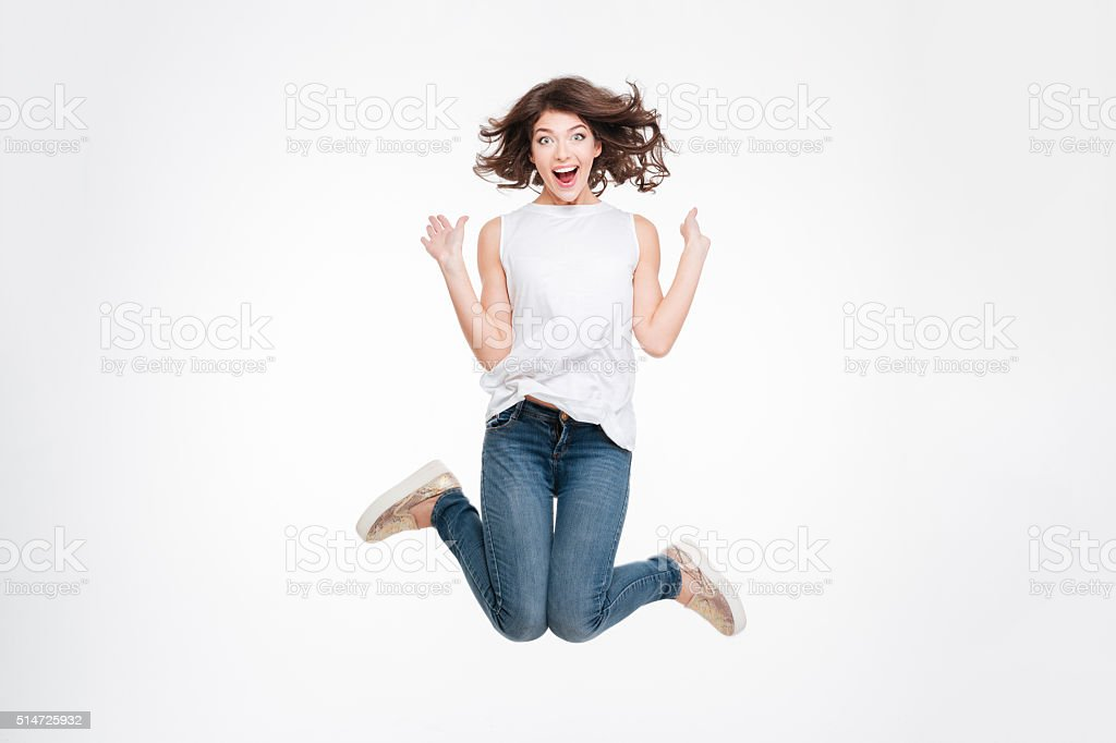 Full length portrait of a cheerful cute woman jumping stock photo