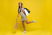 Full length portrait of a happy pretty girl holding shopping bags while running and looking at camera isolated over color background