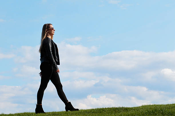 shapely woman walking against the sky outdoor polish girl - whiteway polish outdoor girl stock photos and pictures