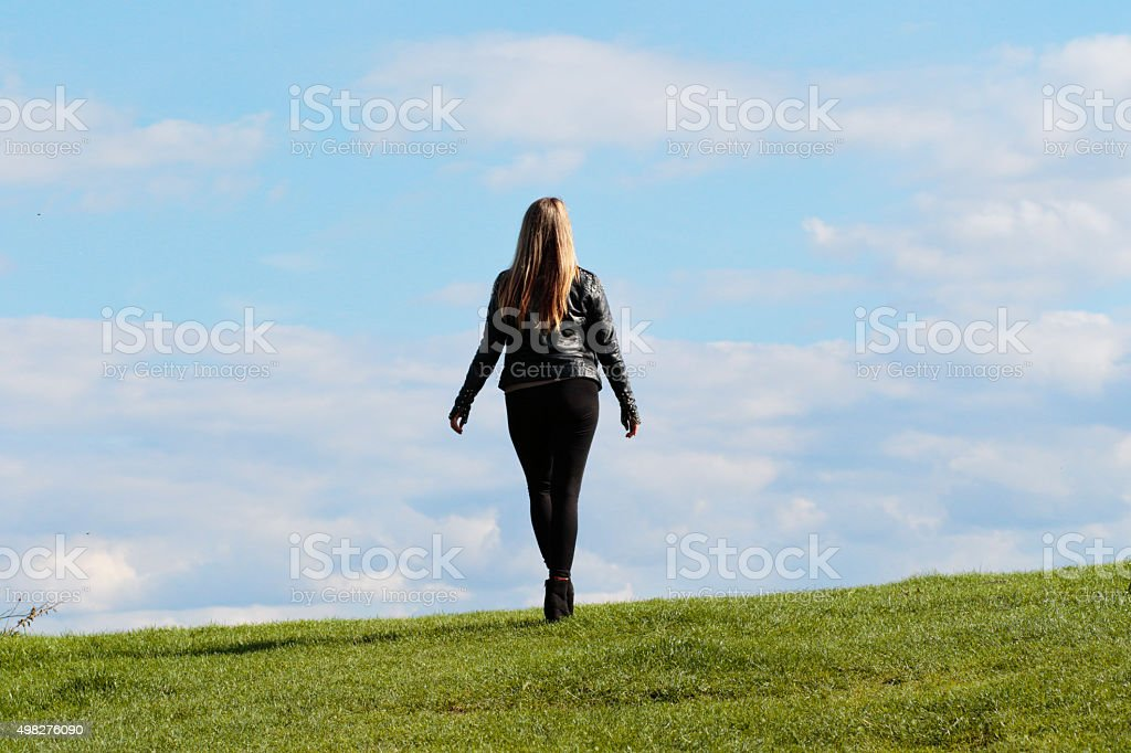 Shapely woman walking away against the sky outdoor Polish girl stock photo