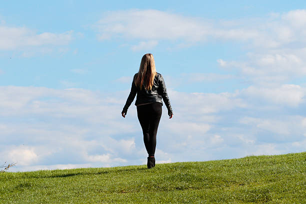 shapely woman walking away against the sky outdoor polish girl - whiteway polish outdoor girl stock photos and pictures