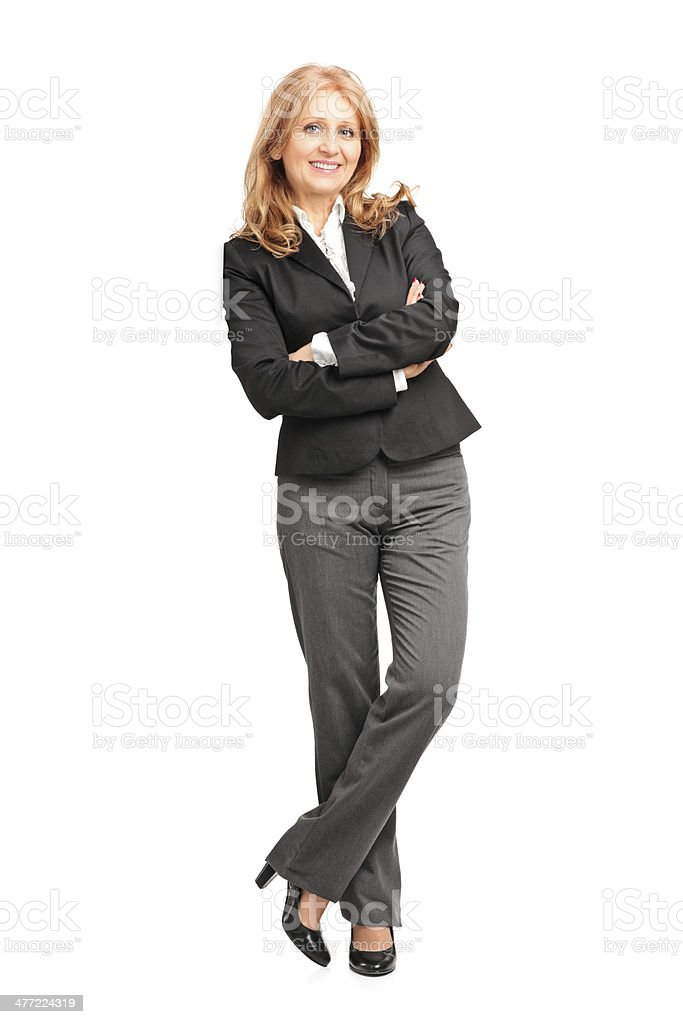 Full length portrait of a smiling businesswoman leaning on wall stock photo