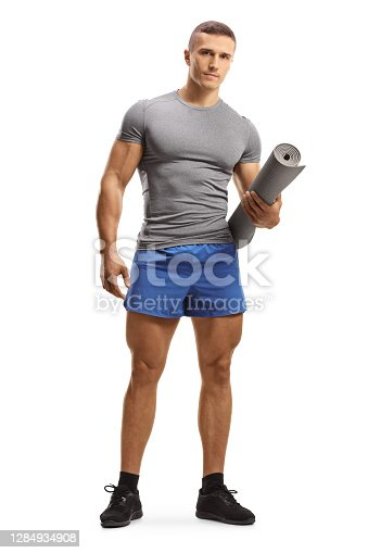 Full length portrait of a young fit man in sportswear holding an exercise mat isolated on white background