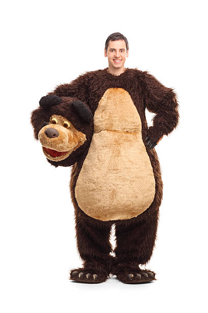 Full length portrait of a young man in bear costume Full length portrait of a young man in a bear costume smiling and looking at the camera isolated on white background mascot stock pictures, royalty-free photos & images