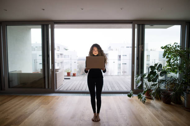 a full length portrait of a young teenage girl standing barefoot at home, holding laptop in front of her. - young girl computer home front imagens e fotografias de stock