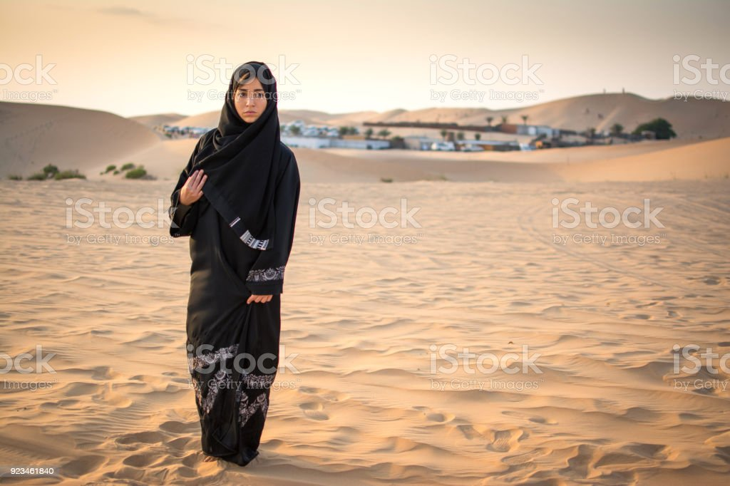 Full length portrait of Arabic woman in traditional black clothes standing in the desert in front of Bedouin village. stock photo