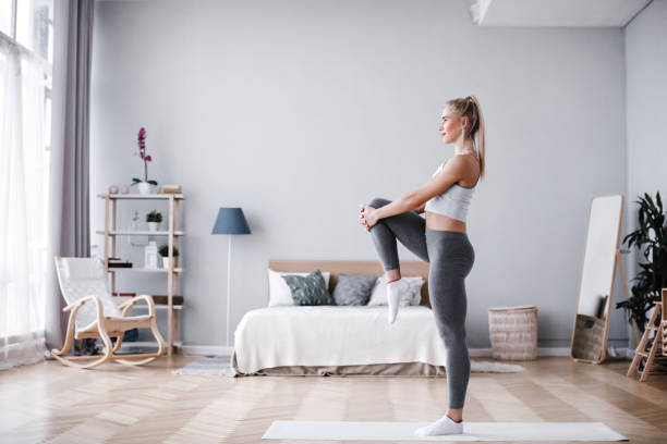 Full length portrait of attractive young woman working out at home, doing pilates exercise on mat. stock photo