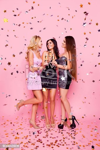 istock Full length portrait of blonde brunette attractive sexy girls in gold confetti celebrating birthday night, bachelor party, holding stemware with champagne, looking to each other, pink background 926643928