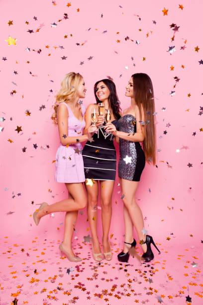 Portrait de pleine longueur de blondes Brunettes jolies filles sexy en or confetti célébration anniversaire de nuit, soirée entre célibataires, tenant des verres à pied avec du champagne, à la recherche à l'autre, rose fond - Photo