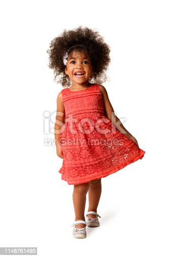 Full length portrait of cheerful african american little girl in dress of the color of the year 2019 living coral, isolated over white background