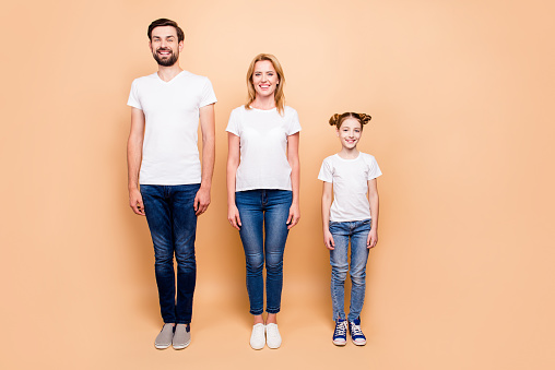Full length portrait of cheerful smiling bearded father and blonde happy mother standing straight with their little daughter in order of hierarchy on beige background