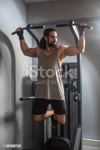 Full length portrait of confident young adult strong man with long curly hair working out in gym, hanging on horizontal bar with hands, doing pull ups with, exercises for triceps. indoor, looking away