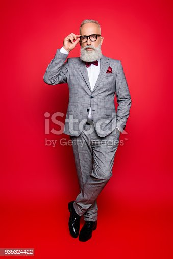Full length portrait of cool stunning stylish trendy old man in checkered jacket and pants, holding hand in pocket and eyelet of glasses on his face, standing leg by foot over red background
