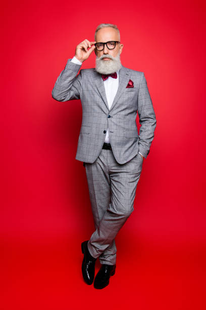 full length portrait of cool stunning stylish trendy old man in checkered jacket and pants, holding hand in pocket and eyelet of glasses on his face, standing leg by foot over red background - tuxedo stock photos and pictures