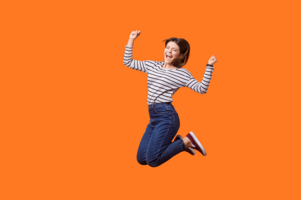 Full length portrait of excited pretty woman with brown hair in casual shirt and denim jumping. indoor studio shot isolated on orange background Full length portrait of excited pretty woman with brown hair in casual shirt and denim jumping celebrating victory, raising fists showing yes gesture. indoor studio shot isolated on orange background mid air stock pictures, royalty-free photos & images