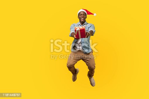925466128 istock photo Full length portrait of extremely happy young man in santa hat and casual denim shirt jumping or flying and giving christmas gift box to camera. 1181449751