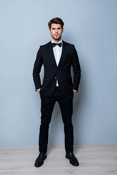 full length portrait of handsome groom holding hands in pockets - tuxedo stock photos and pictures