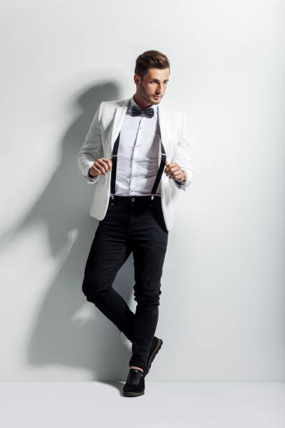 full length portrait of handsome stylish man in white elegant suit posing and leaning at wall - tuxedo stock photos and pictures