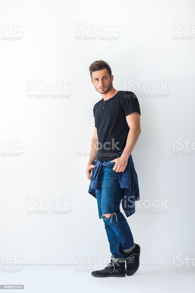 Full length portrait of handsome stylish man leaning at white wall stock photo