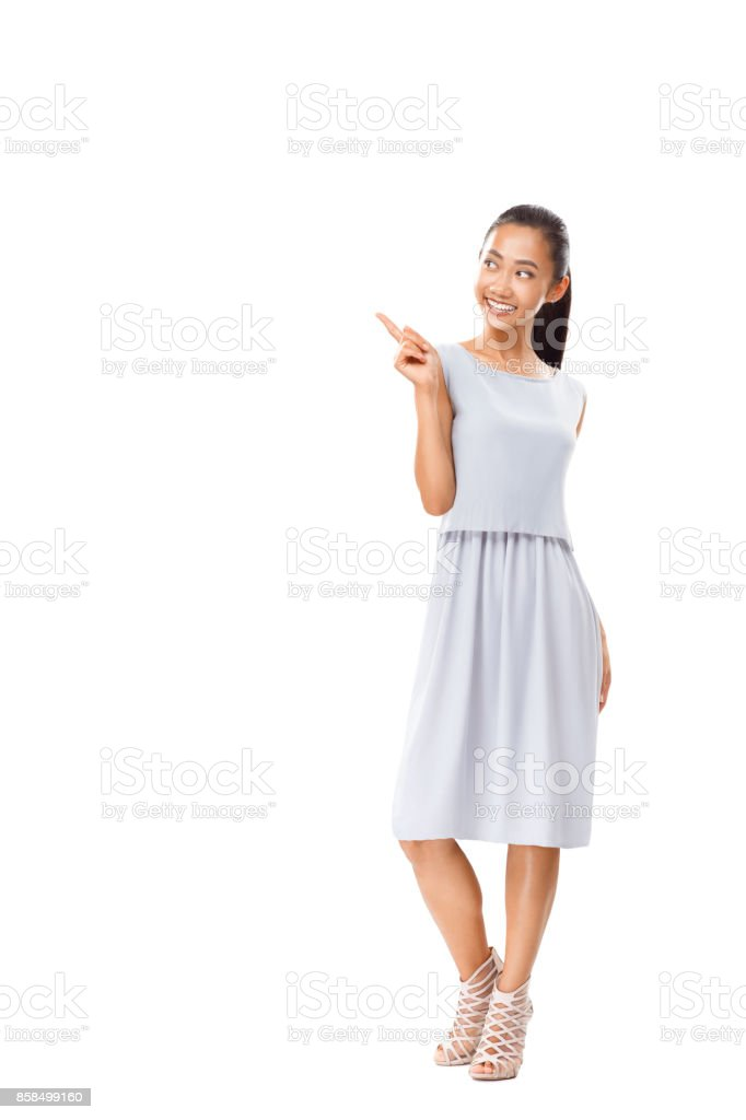 Full length portrait of happy Asian woman pointing finger isolated stock photo