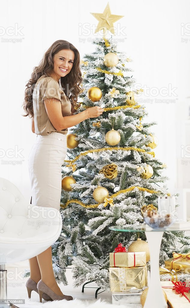 Full length portrait of happy young woman decorating christmas tree Full length portrait of happy young woman decorating christmas tree with christmas ball Adult Stock Photo