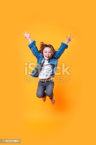 istock Full length portrait of little curly girl jumping over orange background 1162020801