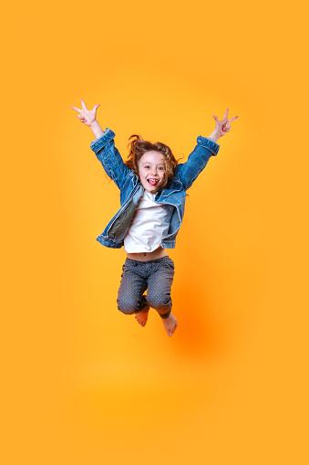 istock Full length portrait of little curly girl jumping over orange background 1162020801
