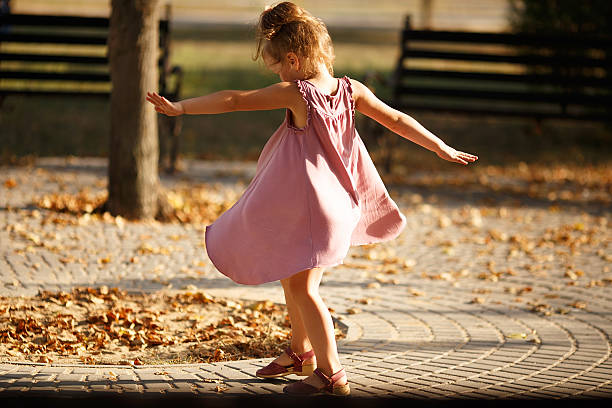 Full length portrait of little girl dancing in the park stock photo