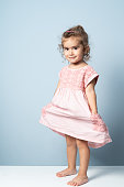 Full length photo of 2,5 years old girl wearing a pink dress on blue background. She is looking at camera and has blond hair. Shot with a full frame mirrorless camera.