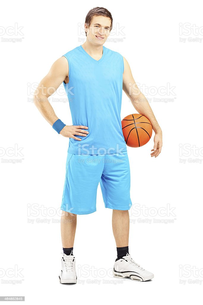 Full length portrait of a male basketball player holding a ball...