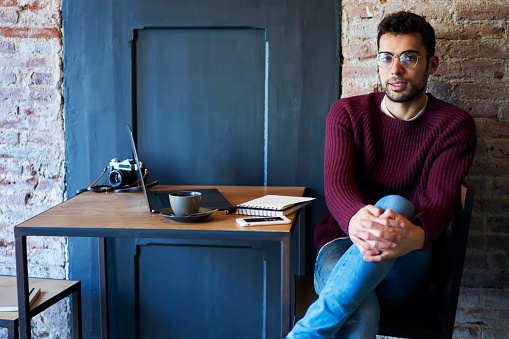 Full length portrait of male journalist in optical spectacles sitting in stylish coffee shop at table with laptop computer and vintage camera.Hipster guy looking at camera during recreating time