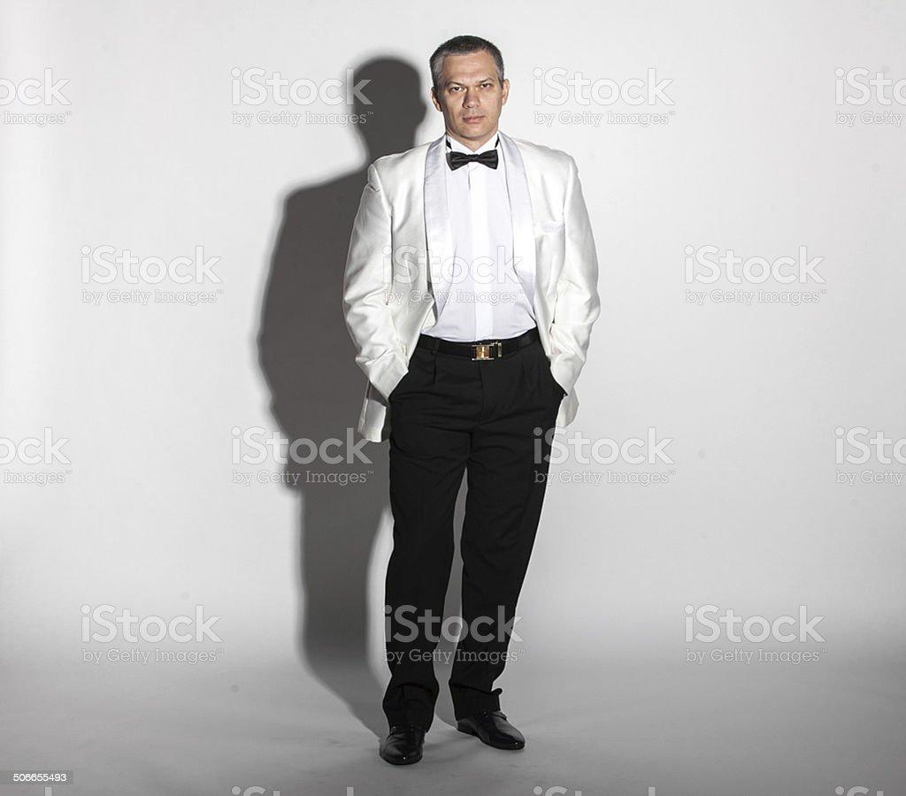 Full length portrait of man in white tuxedo stock photo