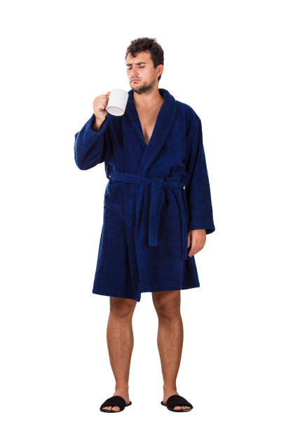 full length portrait of sleepy young man messy hair, wears blue bathrobe holding a cup of tea in his hand, looking confused isolated on white background. - accappatoio foto e immagini stock