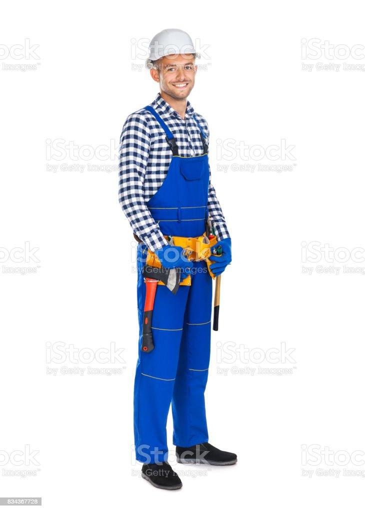 In voller Länge Portrait von lächelnden Bauarbeiter in Uniform und Werkzeuggürtel – Foto