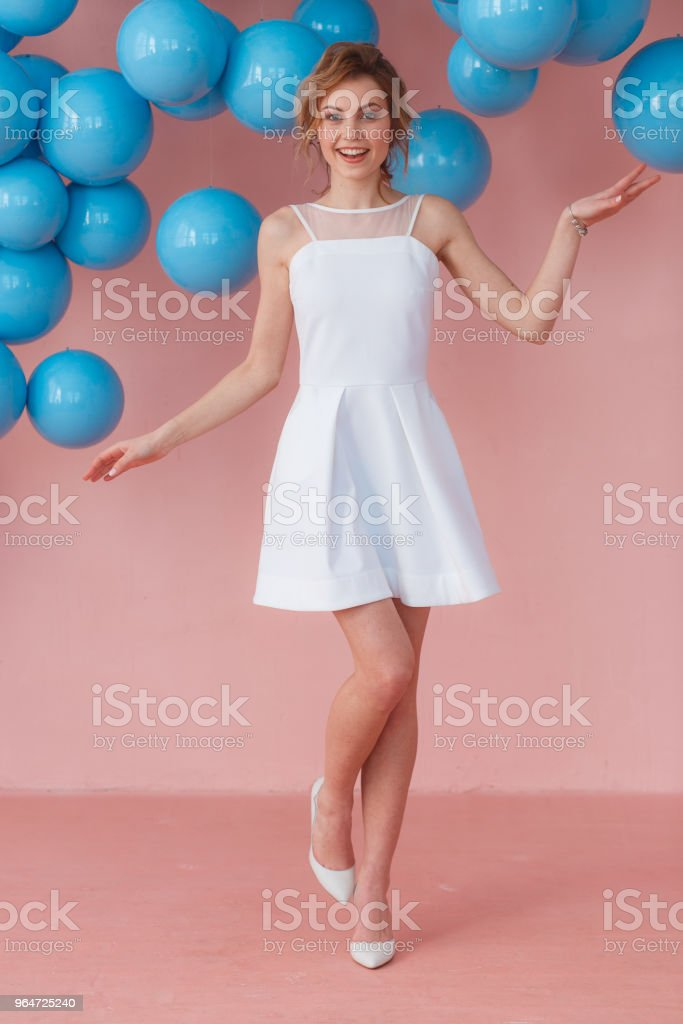 Full length portrait of smiling expression young teen girl posing on pink wall backround decorated with blue balls royalty-free stock photo