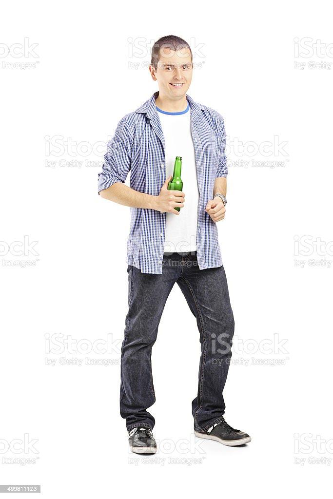 Full length portrait of smiling guy holding a beer bottle stock photo