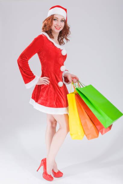 efdf1b25d9 Full Length Portrait of Smiling Sexy Caucasian Ginger Santa Helper Girl  with Plenty of Colorful Shopping