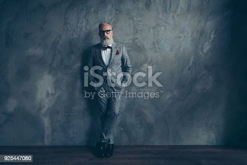 istock Full length portrait of stunning perfect brutal harsh old man in suit with bow-tie holding hands in pockets, leg by foot standing on wooden floor over gray wall 925447080