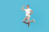 istock Full length portrait of successful overjoyed man in white t-shirt and casual pants jumping with happiness 1204987637