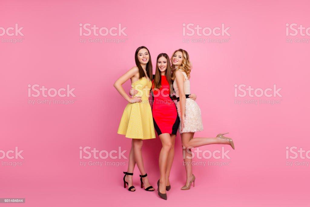 Retrato de longitud completa de tres chicas guapas, tiempo de parte del grupo de niñas con estilo en elegantes vestidos celebrando cumpleaños, día de la mujer, que se divierten, standing sobre fondo rosa, pierna levantada - foto de stock