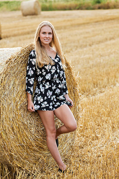 full length portrait of young blonde woman on field - mini dress stock photos and pictures