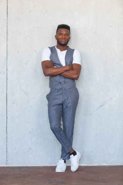 Full length portrait of young handsome african black man posing with crossed arms in grey vest and trousers against a gray concrete wall stock photo