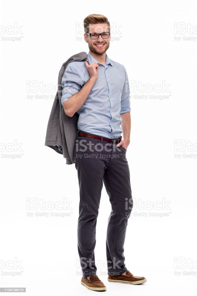 Full length portrait of young man standing on white background stock photo