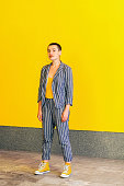 Full length portrait of young short hair beautiful woman in yellow shirt and casual style striped suit standing and looking at camera smiling. indoor studio shot isolated on yellow background.