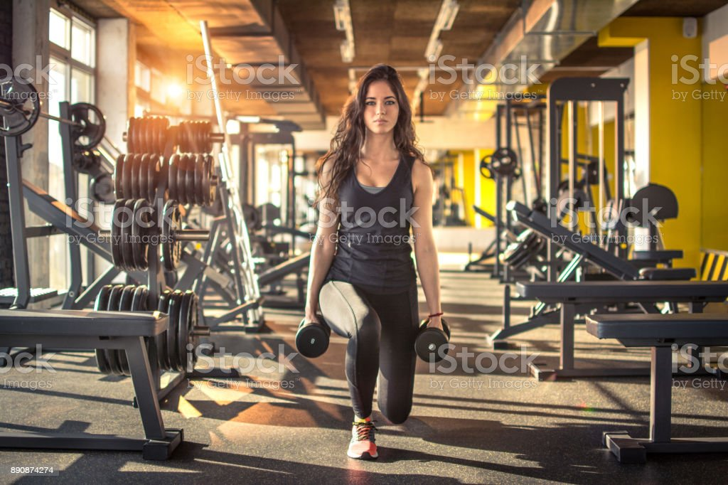 Full length portrait of young slim woman doing lunges with dumbbells in the gym. stock photo