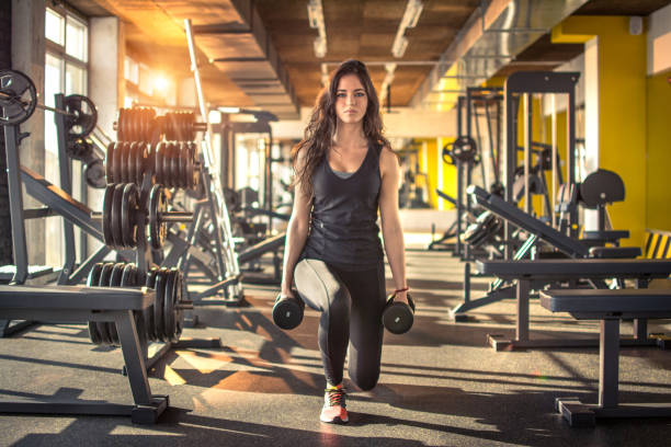 full length portrait of young slim woman doing lunges with dumbbells in the gym. - health club stock photos and pictures