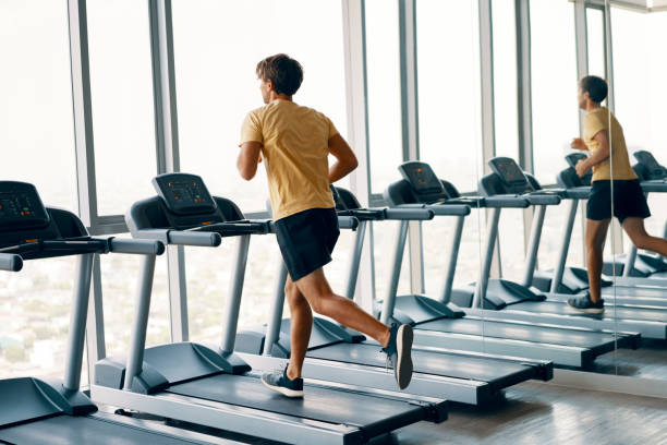 Retrato de longitud completa de un joven deportista corriendo en una cinta de correr en el gimnasio - foto de stock