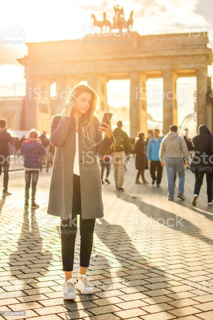 In voller Länge Portrait von junge Frau mit Kopfhörern anhören von Musik auf Handy stehen im Vordergrund des Brandenburger Tors in Berlin, Deutschland. – Foto